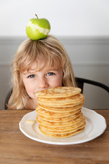 Little girl hiding behing stack of pancakes with an apple on top of her head