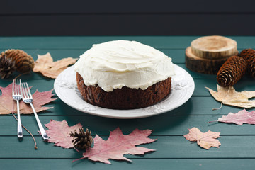 Homemade chocolate fruit cake with cream cheese decorated with dry leaves and cones on dark