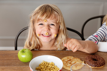 Goofy little girl with cereal loops stuck on face at kitchen table