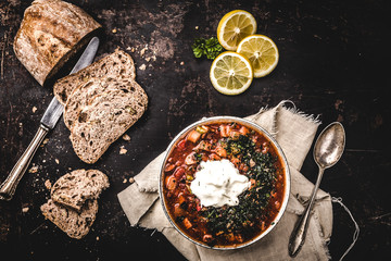 Russian Meat Solyanka Soup In a Bowl with lemon and cream