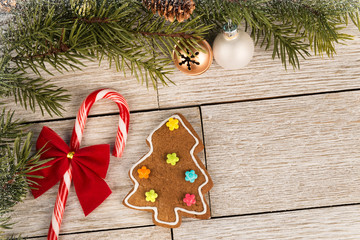 Candy cane, gingerbread cookie and Christmas tree branch on a wooden table. Directly above. Christmas holiday concept.