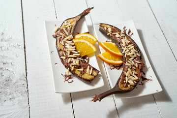 Baked banana dessert with almonds and chocolate with orange on white wooden table.