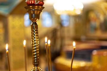 Many burning wax candles in the orthodox church or temple on golden warm background