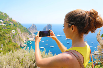 Holidays in Italy! Beautiful young woman take picture with smart phone of Capri Island, Italy