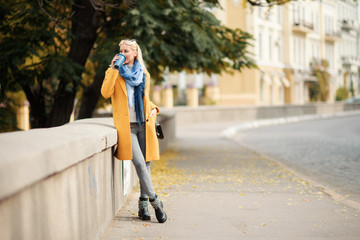 Stylish happy young blond woman in bright yellow coat holds coffee to go. Walking on the street. Portrait of a young cheerful woman at work break. Lifestyle concept