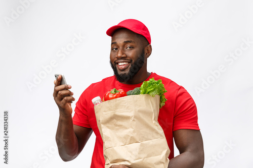 8cb74af4ce0 Delivery Concept - Portrait of Handsome African American delivery man or  courier with grocery package and talking on mobile phone to check the order.