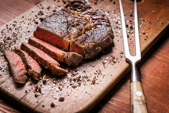 tasty and fresh, very juicy ribbey steak of marbled beef, on a wooden table.