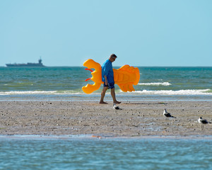 Father walking with lobster float on beach