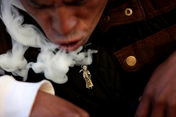 A follower blows smoke from a cigar as part of a cleansing ritual offered to La Santa Muerte (The Saint of Death) who is often depicted as a skeletal grim reaper, in Tepito neighborhood