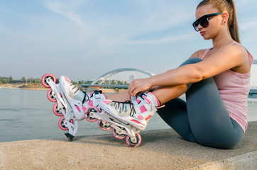 Attractive young woman putting on roller skates outdoors