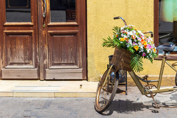A basket with a flowerbed of flowers on the handlebars of a bicycle, the European decor of streets.
