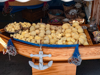 Traditional souvenirs shop on the street, sponges and seashell on table in Gallipoli town of Italy Fototapete