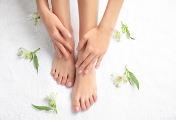 Photo sur cadre textile Pedicure Woman touching her smooth feet on white towel, top view. Spa treatment
