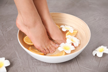 Woman soaking her feet in bowl with water, orange slices and flowers on grey background, closeup. Spa treatment