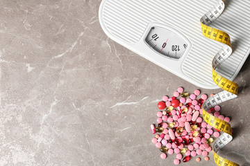 Weight loss pills with scales and measuring tape on gray background, flat lay. Space for text