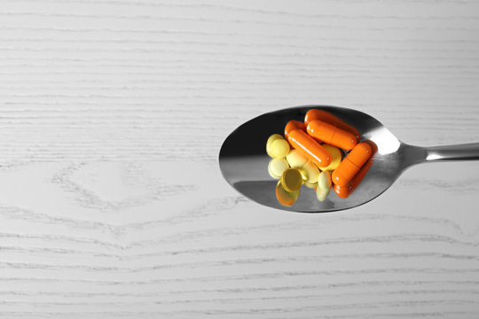 Spoon with weight loss pills on light background, top view