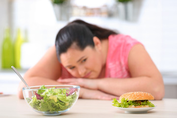 Salad and burger with blurred overweight woman on background. Healthy diet