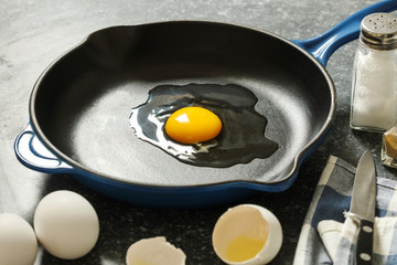 Raw chicken egg in a frying pan.