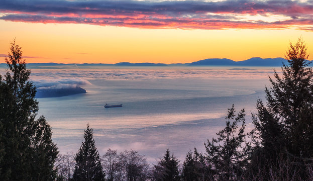 Burrard Inlet Sunset. Scenic view of this British Columbia waterway and the Strait of Georgia from West Vancouver with Vancouver Island on the distant horizon. Seascape background with copy space.