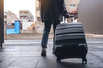 Closeup image of a woman walking while traveling and dragging a black baggage in the outdoors