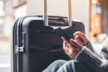 Closeup image of a woman sitting and using mobile phone with a black baggage for traveling