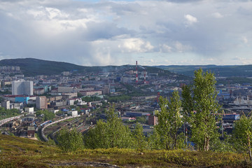 The urban landscape of the Murmansk Soviet architecture and the bright foliage of summer.