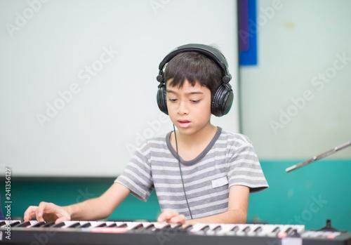 Asian little boy play piano study music classroom