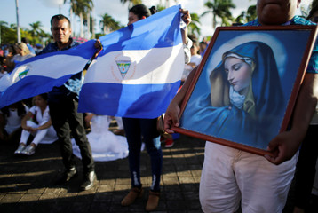 Catholics hold a picture of Virgin Mary and a national flag during a mass for peace in Nicaragua at the Metropolitan Cathedral in Managua