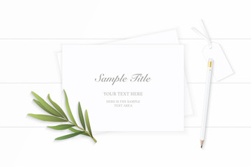 Flat lay top view elegant white Christmas composition paper pencil tag tarragon leaf on wooden background