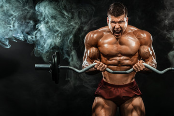 Brutal strong muscular bodybuilder athletic man pumping up muscles with barbell on black background. Workout bodybuilding concept. Copy space for sport nutrition ads.