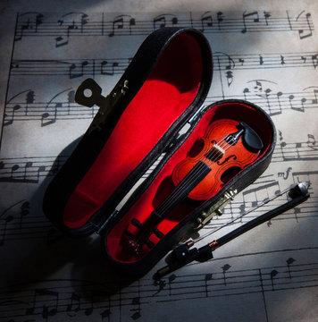 Geige im Geigenkoffer und Musiknoten