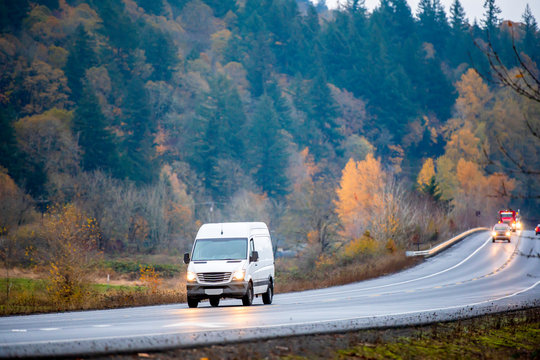 Compact cargo mini van for small business and local delivery driving in winding wet autumn road in rain weather