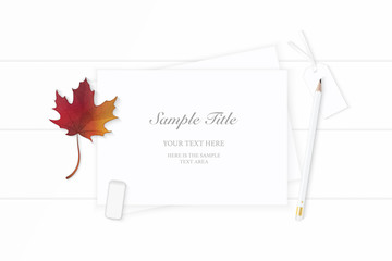 Flat lay top view elegant white Christmas composition paper pencil eraser tag and autumn maple leaf on wooden background