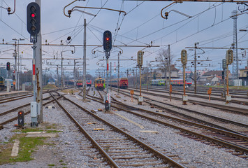 Multiple train tracks leading into station with trafic lights directing before entry into main station