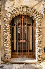 Medieval iron door, adorned with stone