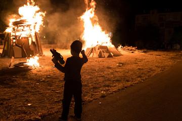 Little jewish religious boy do bonfire at Jewish holiday of Lag Baomer