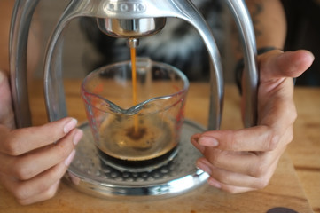 Close-up of espresso pouring from coffee machine.