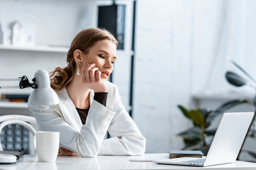 tired businesswoman in white formal wear touching chin while sitting at computer desk at workplace