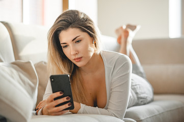 A girl in pajamas is lying on a sofa in a bright room and communicating by video-call with a friend using a wireless earpiece.