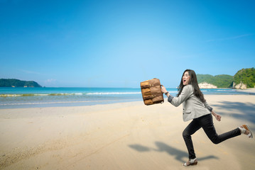 Cheerful asian businesswoman with briefcase going vacation to the beach