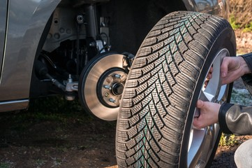 Man is changing summer car wheel, tire before winter
