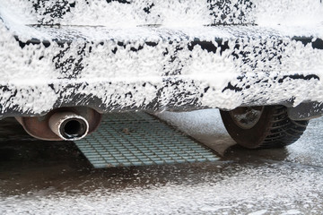 Black car being covered in foam on the self-service car wash. Close-up on the rear bumper, exhaust pipe and wheel