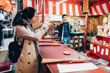 girl holding wooden bamboo gun having fun.