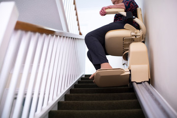 Detail Of Senior Woman Sitting On Stair Lift At Home To Help Mobility