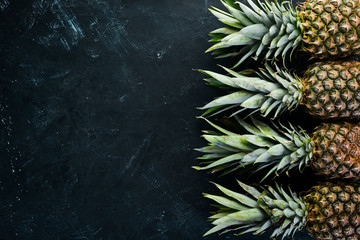 Fresh pineapple on a black stone background. Top view. Free copy space. Wall mural