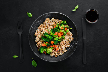 A plate of healthy food. Oatmeal with broccoli, carrots and parsley. Top view. On a black background. Free copy space.