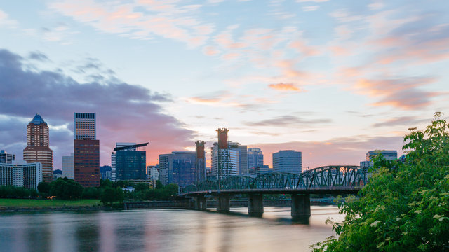 Hawthorne Bridge over Willamette River at sunset with skyline of downtown Portland, USA