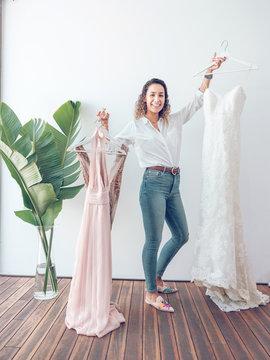 Cheerful woman showing beautiful dresses looking at camera