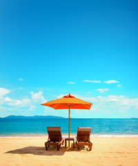 Wall Mural - Two lounge chairs with sun umbrella on a beach