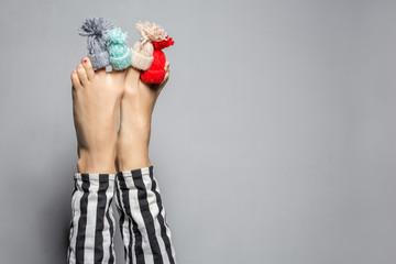 Funny female winter legs on gray wall